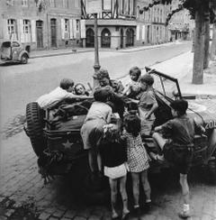 Scatti_di_guerrax_Lee_Miller_Bambini_si_arrampicano_per_raggiungere_la_razione_di_cioccolato_Fred_Feekartxs_dal_conducente_della_jeepx_Dinard_Francia_1944_2